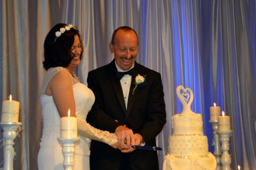 Mid Life couple cutting wedding cake at Cavender Castle